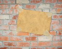 Sheet paper, hanging on brick wall Royalty Free Stock Photos