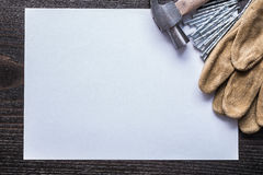 Sheet of paper metal nails claw hammer and leather safety gloves Stock Photo