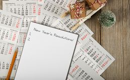 Sheet of paper with new year's resolutions on a new year's background. Top view royalty free stock image