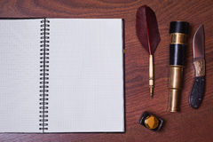A sheet of paper from a notebook, a hunting knife, fountain pen and ink Royalty Free Stock Images
