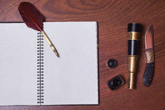 A sheet of paper from a notebook, a hunting knife, fountain pen and ink Stock Photo