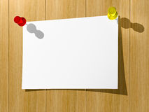 A sheet of paper for notes pinned by two buttons to a wooden wal Royalty Free Stock Image