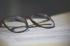 A sheet of paper and a pair of glasses. Home Office Concept and Decoration Stock Photo
