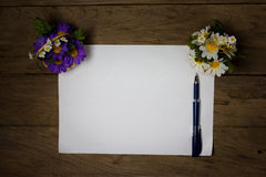 A sheet of paper with a pen on wooden office desk Stock Photos