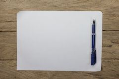 A sheet of paper with a pen on wooden office desk Royalty Free Stock Images