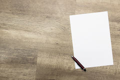 Sheet of paper and pen on wooden table Royalty Free Stock Image