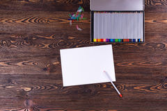 Sheet of paper with a pencil on old brown table. Top view royalty free stock images