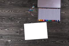 Sheet of paper with a pencil on the old dark table. Colored pencils Stock Photography