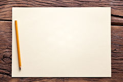 Sheet of paper and pencil on old wooden table. Stock Photo
