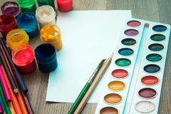 A sheet of paper, pencils and paints. On wooden background. Mock up Stock Images