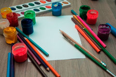 A sheet of paper, pencils and paints. On wooden background. Mock up Stock Photography