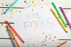 Sheet of paper with phrase. `April fools` and colorful markers on wooden background Stock Photos