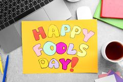 Sheet of paper with phrase. `Happy Fool`s day` on office table. 1st April celebration Stock Photos
