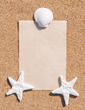 Sheet of paper and seashells on the sand Stock Image