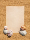 Sheet of paper and seashells on the sand Royalty Free Stock Photo