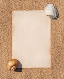 Sheet of paper and seashells on the sand Stock Photos