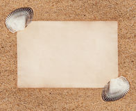 Sheet of paper and seashells on the sand Royalty Free Stock Photography
