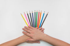 On sheet of paper spread out like a fan of pencils, women`s hands, palms lie on them Stock Image