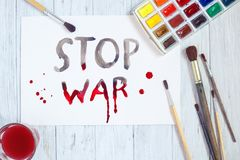 Sheet of paper with STOP WAR text, paintbrushes and watercolor p royalty free stock photos