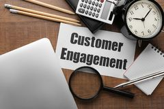 Sheet of paper with text CUSTOMER ENGAGEMENT. On office table stock photography