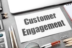 Sheet of paper with text CUSTOMER ENGAGEMENT. On office table stock images