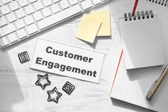 Sheet of paper with text CUSTOMER ENGAGEMENT. On office table stock photo