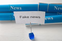 Sheet of paper with text FAKE NEWS on table stock photography