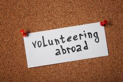 Sheet of paper with text VOLUNTEERING ABROAD. Pinned to cork board Royalty Free Stock Images