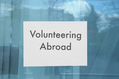Sheet of paper with text VOLUNTEERING ABROAD. On window glass Stock Photo