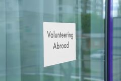 Sheet of paper with text VOLUNTEERING ABROAD  n window glass. Sheet of paper with text VOLUNTEERING ABROAD on window glass Royalty Free Stock Photo