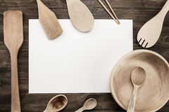 Sheet of paper with utensils on the old wooden background. Mock up Stock Photography