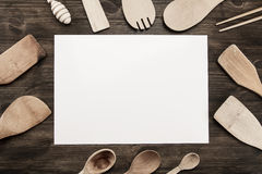 Sheet of paper with utensils on the old wooden background. Mock up Royalty Free Stock Photography