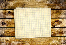 Sheet paper on wooden planks Royalty Free Stock Photos