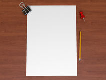 A sheet of paper on a wooden surface. Binder, pin and pencil Stock Image