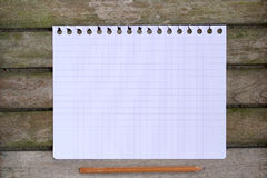 A sheet of paper on a wooden surface. Top view Stock Photography