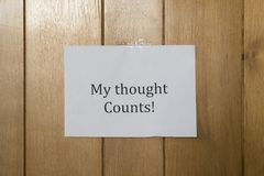 A sheet of paper hanging on the wooden wall royalty free stock photography