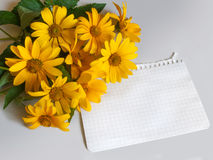 A sheet of paper and yellow flowers on the table background Royalty Free Stock Images