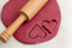 Sheet red dough with a rolling pin and cut out two heart shape cookies, preparing for Valentine's Day Royalty Free Stock Photos