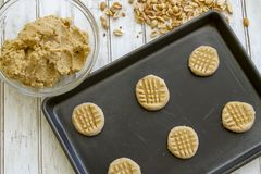 Sheet of unbaked peanut butter cookie dough. Raw peanut butter cookie dough in balls on baking sheet and in bowl with fresh peanuts stock photography