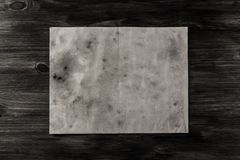 Sheet vintage paper on the aged wooden background. Parchment Royalty Free Stock Photography