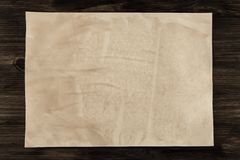 Sheet vintage paper on the aged wooden background. Parchment Stock Image