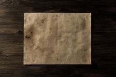 Sheet vintage paper on the aged wooden background. Parchment Stock Images