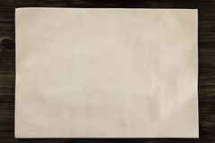 Sheet vintage paper on the aged wooden background. Parchment Royalty Free Stock Image