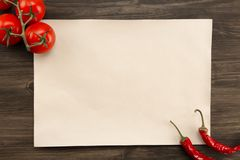 Sheet vintage paper with tomatoes and Chile peppers aged wooden background. Healthy vegetarian food. Recipe, menu, mock up, co Stock Image