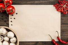 sheet vintage paper with tomatoes, mushrooms, Chile pepper on aged wooden background. Healthy vegetarian food. Recipe, menu, m Stock Photo