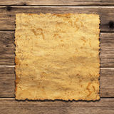 A sheet of vintage paper. On wooden background royalty free stock photo