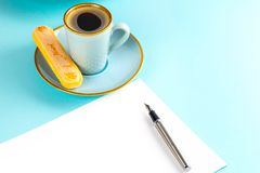 A sheet of white paper is empty on a blue background with an ink pen . Copy space. stock images
