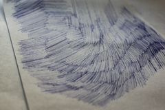 A sheet of white paper with painted dirty strokes, a blue ballpoint pen. Blurred background, shallow depth of field. Drawn record. Incomprehensible scribbles stock photography