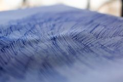 A sheet of white paper with painted dirty strokes, a blue ballpoint pen. Blurred background, shallow depth of field. Drawn record. Incomprehensible scribbles stock image