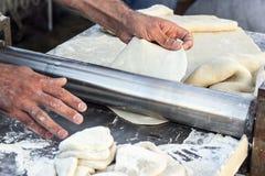 Sheeter för bakelse för kockdanandedeg på bageribagaren som bildar forma deg, rullade process för händer för closeup för tabell f royaltyfria foton